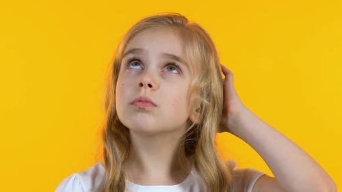 Small Schoolgirl Thinking, Shrugging Shoulders Remembering Necessary Information