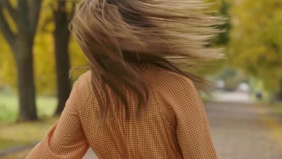 Thumbnail for Smiling Caucasian Woman with Long Brown Hair and Green Eyes Spinning in the Autumn Park. Elegant