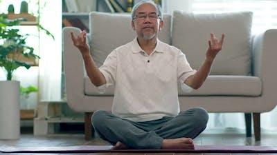 Asian elderly senior man doing yoga for meditation on yoga mat in living room