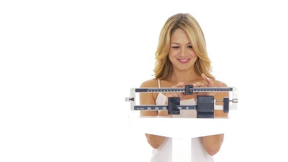Thumbnail for Happy young woman weighing herself on scale