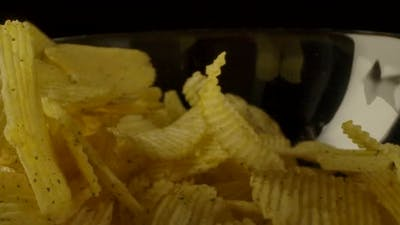 Ribbed Chips Falling Into Bowl