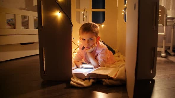 Dolly Shot of Boy Reading Book While Lying in Toy House or Tent at Night