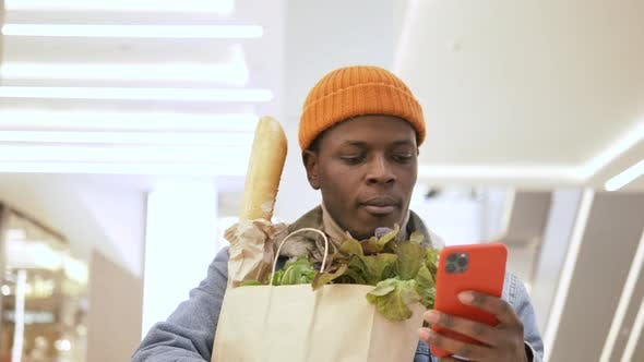 Black Man in Hat Holds Paper Bag with Healthy Products