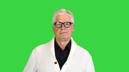 Senior Man Wearing a Cardigan Standing and Looking To Camera Doing Nothing on a Green Screen Chroma