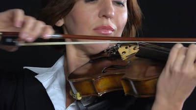 Woman Bows Over the Strings of a Violin