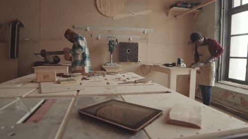 Two Handymen Working in Carpentry Workshop