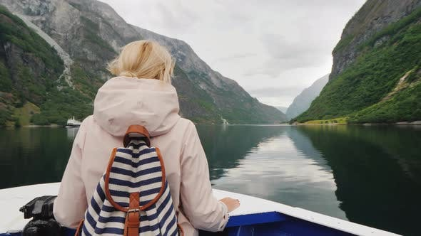 Thumbnail for A Fascinating Journey Through the Fjords of Norway. Woman Stands on the Prow of a Cruise Ship