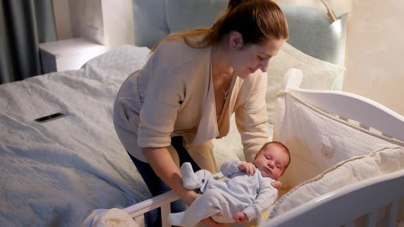 Beautiful Young Caring Mother Putting Her Newborn Baby Boy in Crib and Covering Him with Warm