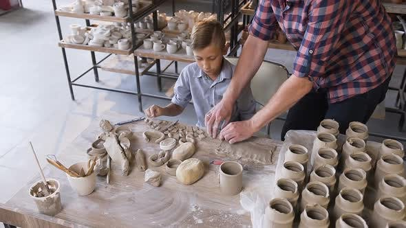 Thumbnail for Caucasian Caring Father Helping Little Son Making Ceramic Vase