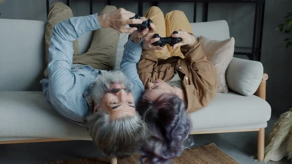 Crazy Adult Gamers Joyful Couple Playing Videogame and Laughing Doing Highfive Indoors in Apartment