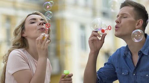 Pretty female and male blowing soap bubbles and kissing, carefree love, date