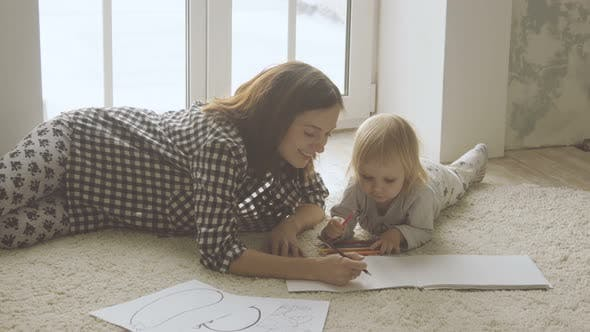 Thumbnail for Mother with little daughter draws with pencils in album