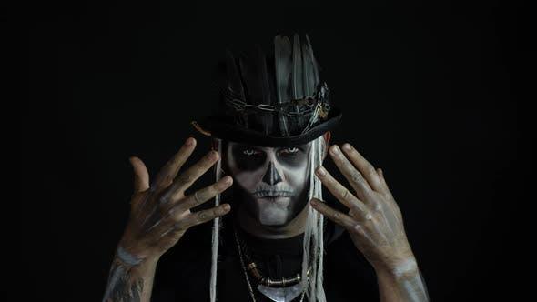 Scary Guy in Carnival Costume of Halloween Skeleton Against Black Background. Man Skull Makeup