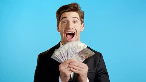 Thumbnail for Amazed Happy Excited Businessman with Money - U.S. Currency Dollars Banknotes on Blue Studio Wall