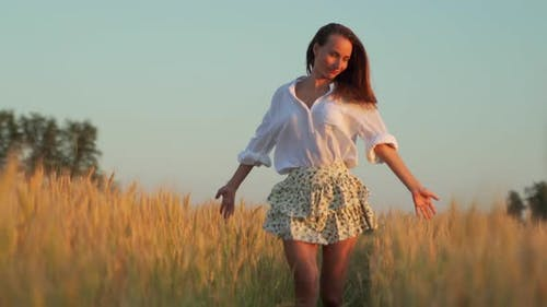 Young Woman in a Skirt and a White Shirt Walks Through a Wheat Field with Hands Outstretched