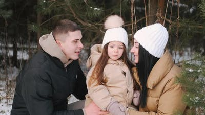 Parents with Daughter Walking in Forest in Winter