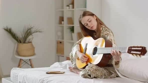 Thumbnail for Happy Woman in Pajama Playing Guitar at Home