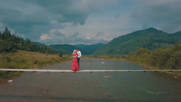 Thumbnail for Сouple Stands on Bridge Over a Mountain River. Love of Man and a Woman