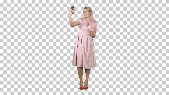 Mature woman wearing light pink dress making selfie, Alpha Channel