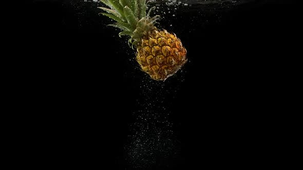 Cover Image for Tropical Fruit Pineapple Falling Into Water with Splash and Air Bubbles on Black Background