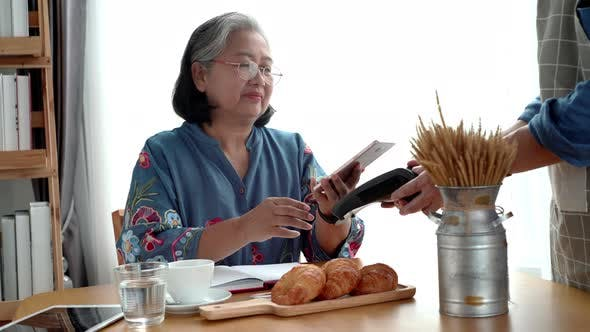 Cover Image for Elderly Asian Woman Using a Mobile Phone Smart Payment 03