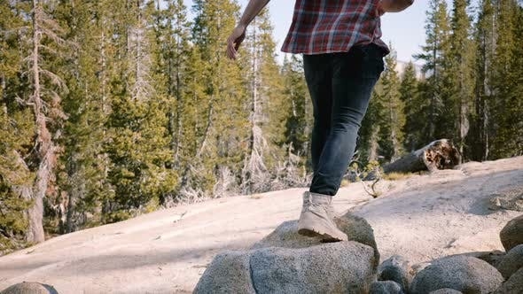 Thumbnail for Camera Tilts Up From Male Legs in Desert Shoes To Happy Local Man Hiking Alone at Beautiful Yosemite