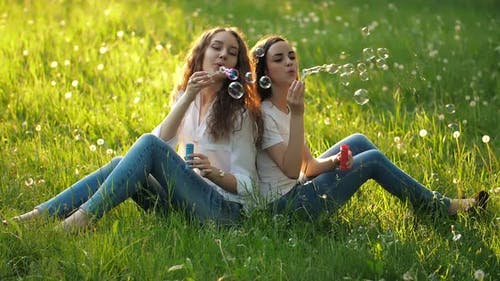 Girlfriends Sitting on the Grass and Blowing Bubbles