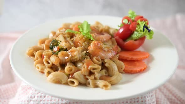 Stir fried macaroni with shrimp, squid, tomatoes, peppers and broccoli on a white plate