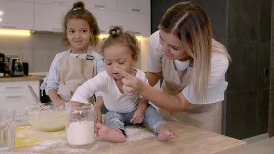 Mother with Kids at the Kitchen Cooking