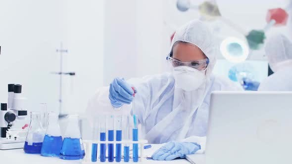 Thumbnail for Female Scientist in Modern Laboratory Wearing a Coverall Equipment Taking Samples