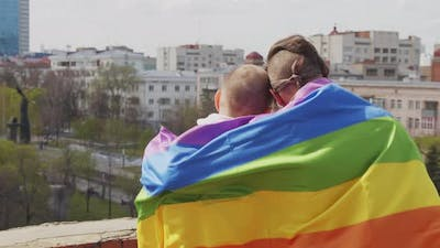Gay Couple with Rainbow Flag Looking at Cityscape