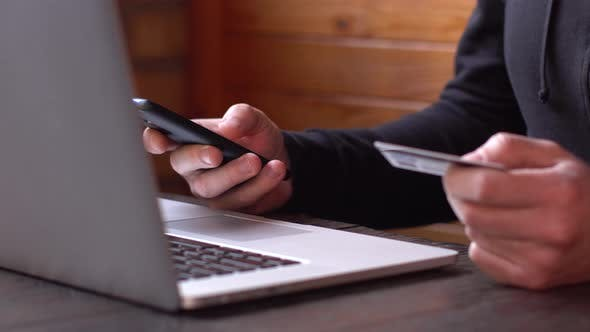 Cover Image for Businessman in a Black Hoodie Making Online Payment with Credit Card and Smartphone, Online Shopping