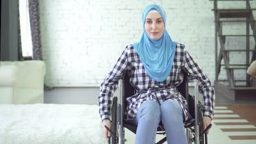 Beautiful Young Woman in Hijab Disabled Person Wheelchair in Apartment