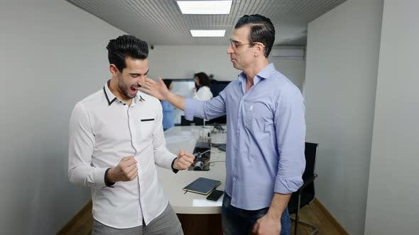 Positive Middle Eastern Man Supporting Cheerful Colleague Rejoicing Success