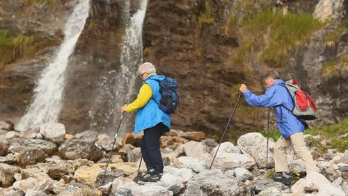 Hikers Crossing Stream Near Waterfall