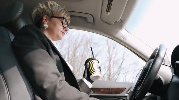 Thumbnail for A Businesswoman in Glasses Is Working and Drinking a Coffee in a Car