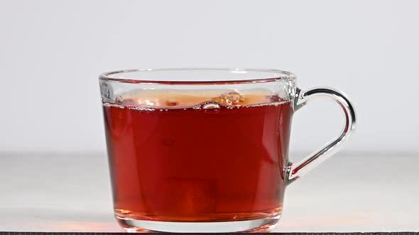 Throwing brown sugar cubes in glass cup full of black tea over white background