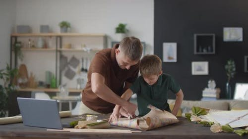 Father And Son Making Paper Kite