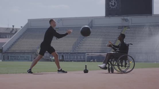 Thumbnail for Wheelchaired Athlete and Trainer Throwing Medicine Ball