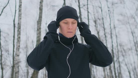 Thumbnail for A Young Man on a Morning Jog Holds Headphones in His Hands and Inserts It Into His Ears Before