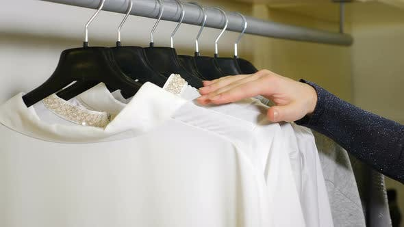 Closeup Shot of Female Hand Running on Clothing Hangers Rail Rack and Looking for Garment at Clothes