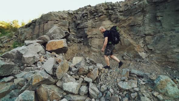 Thumbnail for Extreme Tourist with a Backpack on His Shoulders is Walking Along the Rocks
