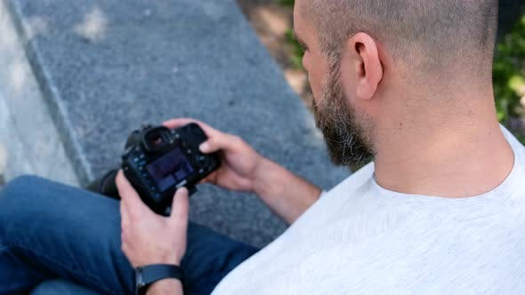 Thumbnail for Bearded Photographer Looks at Photos on His Digital Camera