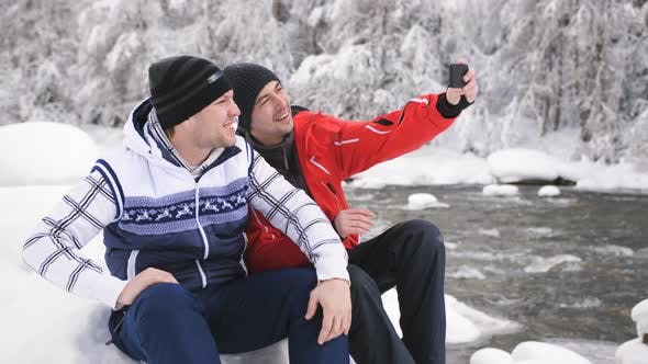 Thumbnail for Two Cheerful Men in the Winter the River Communicate with Friends on the Smartphone with Video Call