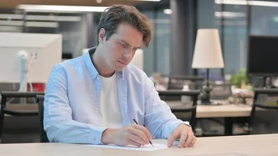 Man Writing on Paper in Office