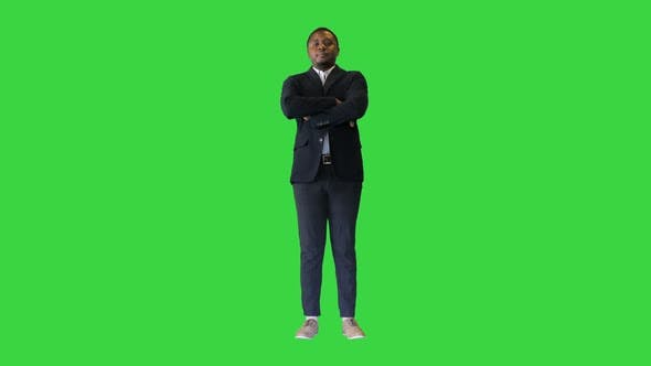 Young African American Man with Crossed Arms Pointing a Finger for the Camera on a Green Screen