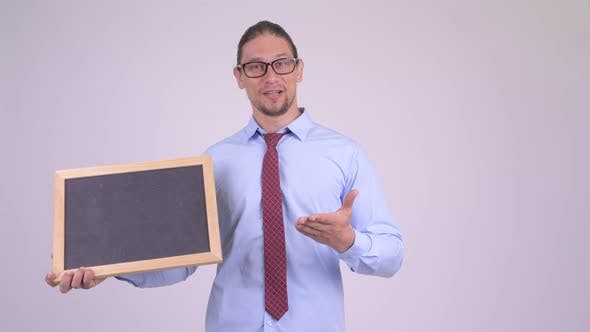 Happy Handsome Businessman Holding Blackboard and Giving Thumbs Up