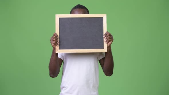 Young African Man Showing Blackboard