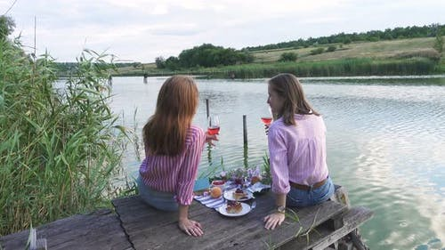 Two Girls Enjoying Picnic On A Wooden Pier 4