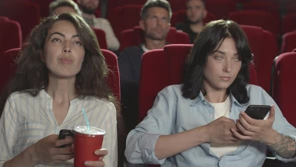 Thumbnail for Two Women Using Cellphones in Cinema
